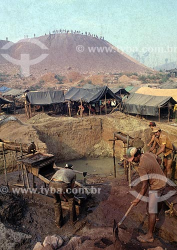 Assunto: Trabalhadores no garimpo de Serra Pelada - considerado o maior garimpo a céu aberto do mundo na década de 80 - com um acampamento ao fundo / Local: Distrito de Serra Pelada - Curionópolis - Pará (PA) - Brasil / Data: Década de 80