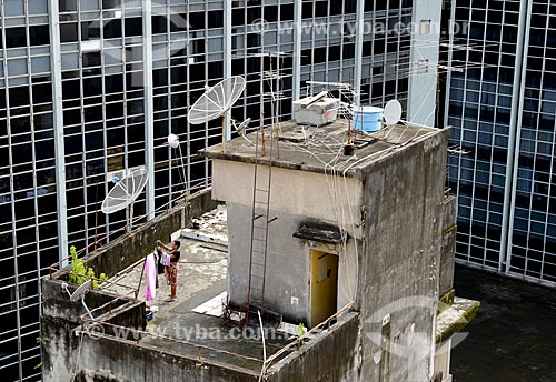 Assunto: Mulher estendendo roupas no terraço de um prédio residencial entre prédios comerciais / Local: Centro - Rio de Janeiro (RJ) - Brasil / Data: 02/2013
