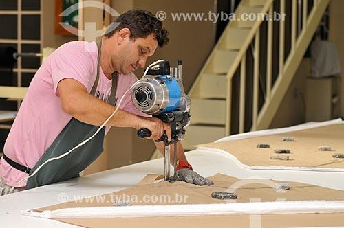 Cortador com máquina de corte de tecido trabalhando na produção de roupas  - Ibirá - São Paulo - Brasil