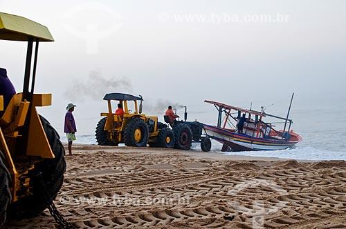 Trator puxando barco de pesca para a areia na Praia de Farol de São Thomé - Pescadores utilizam tratores para puxar e empurrar as embarcações do mar para a areia por não possuírem porto para o atracamento dos barcos  - Campos dos Goytacazes - Rio de Janeiro - Brasil