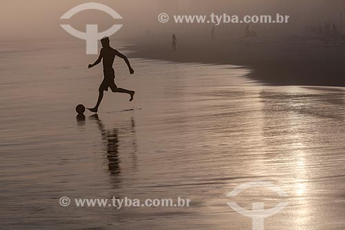 Assunto: Jovem jogando futebol na Praia da Barra da Tijuca durante maresia no inverno / Local: Barra da Tijuca - Rio de Janeiro (RJ) - Brasil / Data: 07/2013