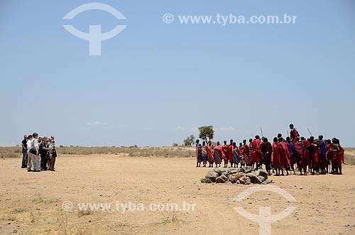 Turistas assistindo à tribo Masai dançando o Adumu - também conhecida como dança do pulo - é uma competição entre eles e também uma dança de boas-vindas - no Parque Nacional de Amboseli