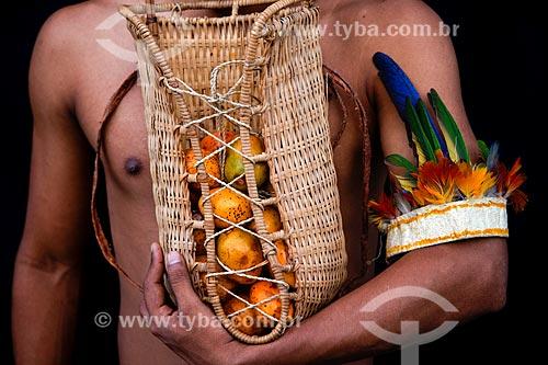 Assunto: Índio da tribo ticuna segurando cesto de palha com mari (Geoffroea spinosa) - também conhecido com umari / Local: Amazonas (AM) - Brasil / Data: 01/2014