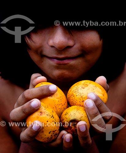 Assunto: Criança indígena segurando mari (Geoffroea spinosa) - também conhecido com umari / Local: Amazonas (AM) - Brasil / Data: 01/2014