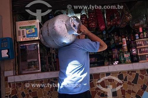 Assunto: Homem carregando botijão de gás em frente a bar no Morro do Turano / Local: Rio de Janeiro (RJ) - Brasil / Data: 04/2011