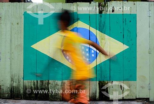 Assunto: Menino correndo com muro decorado durante a Copa do Mundo no Brasil ao fundo / Local: Manaus - Amazonas (AM) - Brasil / Data: 06/2014