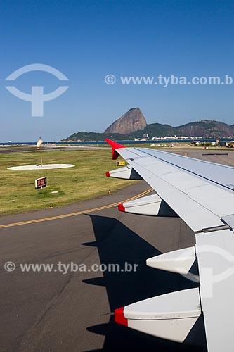 Detalhe de asa de avião durante aterrissagem no Aeroporto Santos Dumont com o Pão de Açúcar ao fundo  - Rio de Janeiro - Rio de Janeiro (RJ) - Brasil
