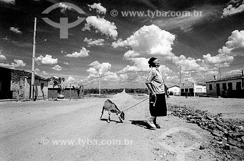 Mulher carregando cabra no sertão  - Canudos - Bahia (BA) - Brasil