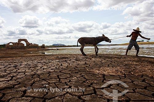 Homem puxando burro no Açude Cocorobó durante o período de seca com as ruínas da Igreja de Santo Antônio da Velha Canudos ao fundo  - Canudos - Bahia (BA) - Brasil