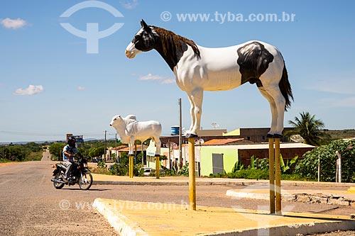 Estátua de um cavalo e boi próximo ao pórtico da cidade de Cedro ao fundo - Rodovia PE-475  - Cedro - Pernambuco (PE) - Brasil