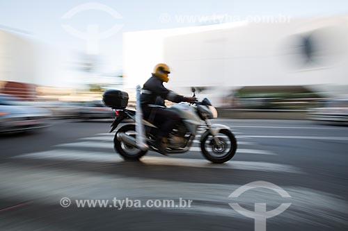 Motociclista passando sobre a faixa de pedestre e ao fundo Biblioteca Municipal Governador Leonel de Moura Brizola - Centro Cultural Oscar Niemeyer  - Duque de Caxias - Rio de Janeiro (RJ) - Brasil
