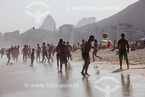 Pessoas jogando futebol na orla da Praia do Leme com Morro Dois Irmãos e a Pedra da Gávea ao fundo  - Rio de Janeiro - Rio de Janeiro (RJ) - Brasil
