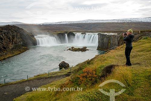 Mulher fotografando queda-dágua próximo à cidade de Akureyri  - Akureyri - Northeastern Region - Islândia