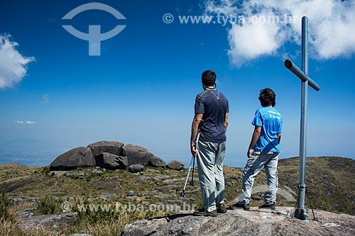 Homens e cruz no cume do Morro do Açu com as formações rochosas conhecida com Castelos do Açu ao fundo  - Petrópolis - Rio de Janeiro (RJ) - Brasil