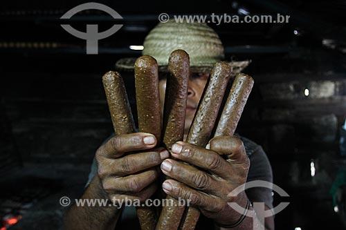 Ribeirinho segurando Bastões de Guaraná - produção típica da região de Maués  - Maués - Amazonas (AM) - Brasil