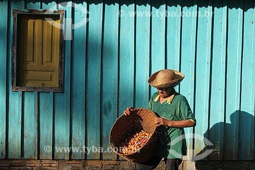 Homem ribeirinho carregando cesto de palha com frutos do Guaraná (Paullinia cupana)  - Maués - Amazonas (AM) - Brasil