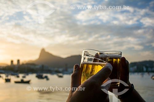 Brinde com cerveja no pôr do sol na Mureta da Urca - Morro do Corcovado ao fundo  - Rio de Janeiro - Rio de Janeiro (RJ) - Brasil