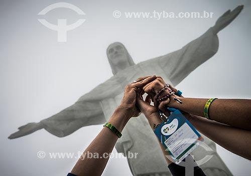 Detalhe de mãos unidas em prece com o Cristo Redentor ao fundo durante a Jornada Mundial da Juventude (JMJ)  - Rio de Janeiro - Rio de Janeiro (RJ) - Brasil