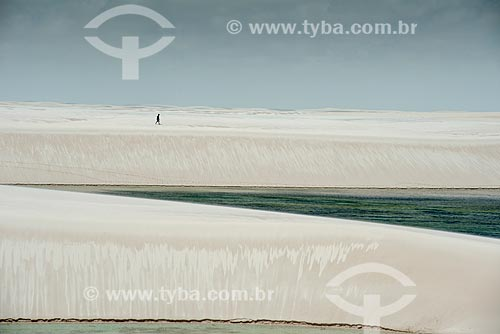 Homem caminhando às margens da Lagoa América no Parque Nacional dos Lençóis Maranhenses  - Santo Amaro do Maranhão - Maranhão (MA) - Brasil