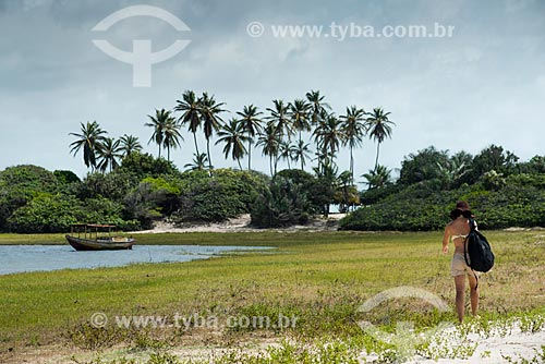 Mulher caminhando às margens da Lagoa do Santo Amaro - Parque Nacional dos Lençóis Maranhenses  - Santo Amaro do Maranhão - Maranhão (MA) - Brasil