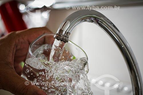 Torneira aberta enchendo copo com água  - Brasil
