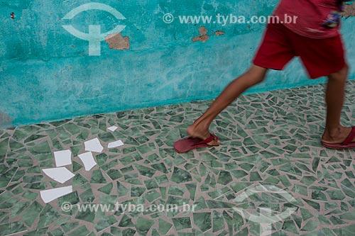 Menino brincando em calçamento com piso de cacos de cerâmica - típico de casa em Juazeiro do Norte  - Juazeiro do Norte - Ceará (CE) - Brasil