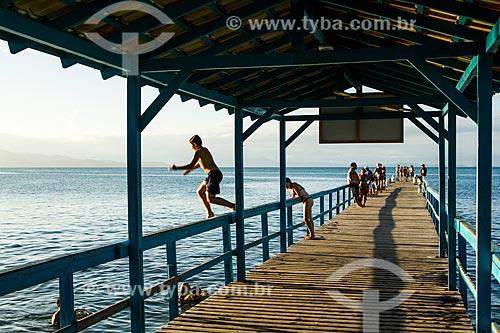 Banhista pulando no mar a partir do píer da Praia de Canasvieiras  - Florianópolis - Santa Catarina (SC) - Brasil