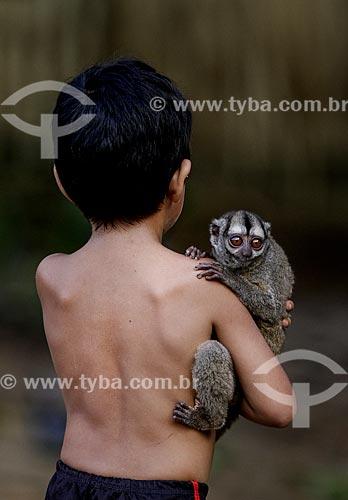 Garoto ribeirinho segurando um macaco-da-noite (Aotus Trivirgatus)  - Amazonas (AM) - Brasil