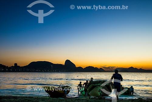 Pescadores da colônia de pescadores Z-13 - no Posto 6 da Praia de Copacabana - colocando o barco no mar com o Pão de Açúcar ao fundo  - Rio de Janeiro - Rio de Janeiro (RJ) - Brasil