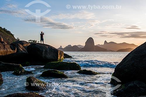 Homem observando o pôr do sol na Praia do Forte Barão do Rio Branco - também conhecida como Praia de Fora - com o Pão de Açúcar ao fundo  - Niterói - Rio de Janeiro (RJ) - Brasil
