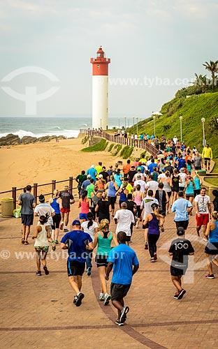 Pessoas correndo no calçadão da Praia de uMhlanga com o farol ao fundo  - Durban - Província KwaZulu-Natal - África do Sul