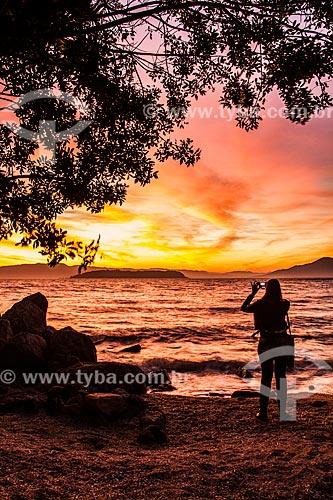 Mulher fotografando o pôr do sol na Praia da Ponta do Sambaqui  - Florianópolis - Santa Catarina (SC) - Brasil