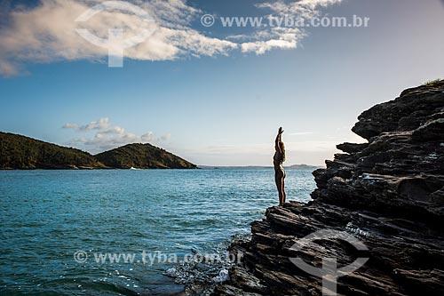Mulher praticando Yoga na Praia de João Fernandinho - movimento ekam (saudação ao sol)  - Armação dos Búzios - Rio de Janeiro (RJ) - Brasil