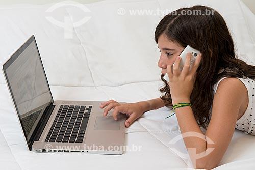Menina utilizando computador e telefone celular  - Rio de Janeiro - Rio de Janeiro (RJ) - Brasil