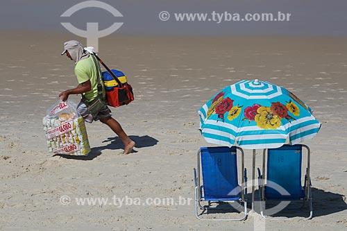 Vendedor de biscoito de polvilho Globo próximo à cadeiras de praia com guarda-sol na Praia de Ipanema  - Rio de Janeiro - Rio de Janeiro (RJ) - Brasil