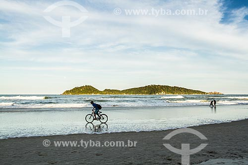 Ciclista na orla da Praia do Campeche com a Ilha do Campeche ao fundo  - Florianópolis - Santa Catarina (SC) - Brasil