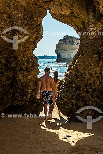 Casal passando entre a fenda de rocha na Praia de Alvor  - Concelho de Portimão - Distrito de Faro - Portugal