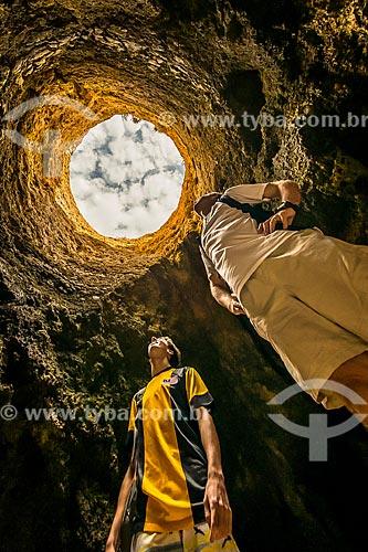 Homens observando o buraco no rochedo da Prainha na freguesia de Alvor  - Concelho de Portimão - Distrito de Faro - Portugal