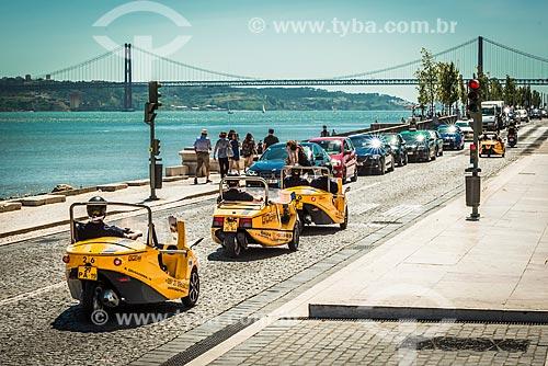 Turistas no GoCAR - sistema de passeio turístico através de carro guiado por GPS - às margens do Rio Tejo com a onte Vinte e Cinco de Abril ao fundo  - Lisboa - Distrito de Lisboa - Portugal