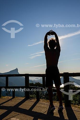 Homem se alongando na Vista Chinesa - Parque Nacional da Tijuca - com o Cristo Redentor ao fundo  - Rio de Janeiro - Rio de Janeiro (RJ) - Brasil