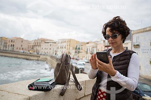 Mulher usando smartphone na Ilha Ortígia - às margens do Mar Jônico  - Siracusa - Província de Siracusa - Itália