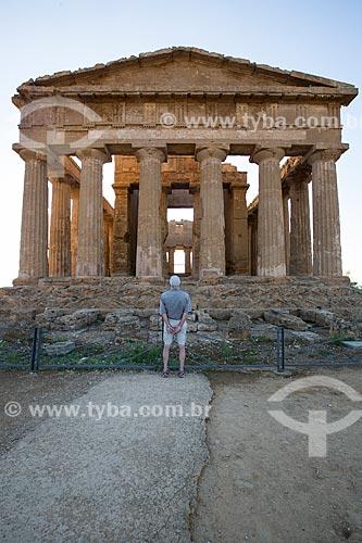 Turista observando o Templo de Concórdia no Valle dei Templi (Vale dos Templos) - antiga cidade grega de Akragas  - Agrigento - Província de Agrigento - Itália