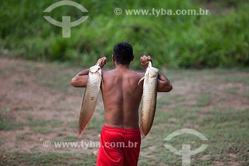 Homem ribeirinho carregando o peixe aruanã  - Manaus - Amazonas (AM) - Brasil