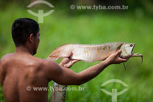 Homem ribeirinho segurando o peixe aruanã  - Manaus - Amazonas (AM) - Brasil