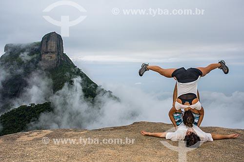 Casal executando movimento de Yoga acrobática na Pedra Bonita com a Pedra da Gávea ao fundo  - Rio de Janeiro - Rio de Janeiro (RJ) - Brasil