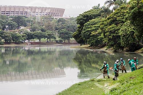 Trabalhadores fazendo a poda da grama às margens da Lagoa da Pampulha com o Estádio Governador Magalhães Pinto (1965) - também conhecido como Mineirão - ao fundo  - Belo Horizonte - Minas Gerais (MG) - Brasil