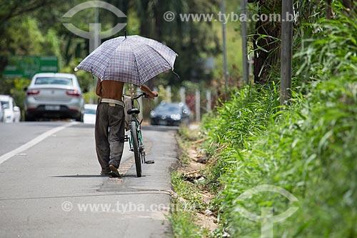 Ciclista com guarda-chuva no acostamento da Rodovia Lucio Meira (BR-393) próximo ao KM-177 - sentido norte  - Três Rios - Rio de Janeiro (RJ) - Brasil