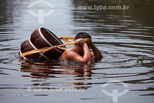 Homem carregando piaçava (Attalea funifera) pelo Rio Negro  - Barcelos - Amazonas (AM) - Brasil