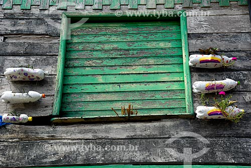 Janela de casa com garrafas PET recicladas transformadas em floreiras  - Novo Airão - Amazonas (AM) - Brasil