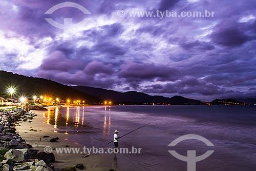 Homem pescando na Praia da Armação ao anoitecer  - Florianópolis - Santa Catarina (SC) - Brasil